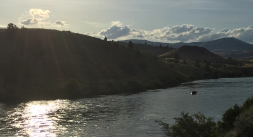 Evening light on the Deschutes and a drift boat gliding downstream.